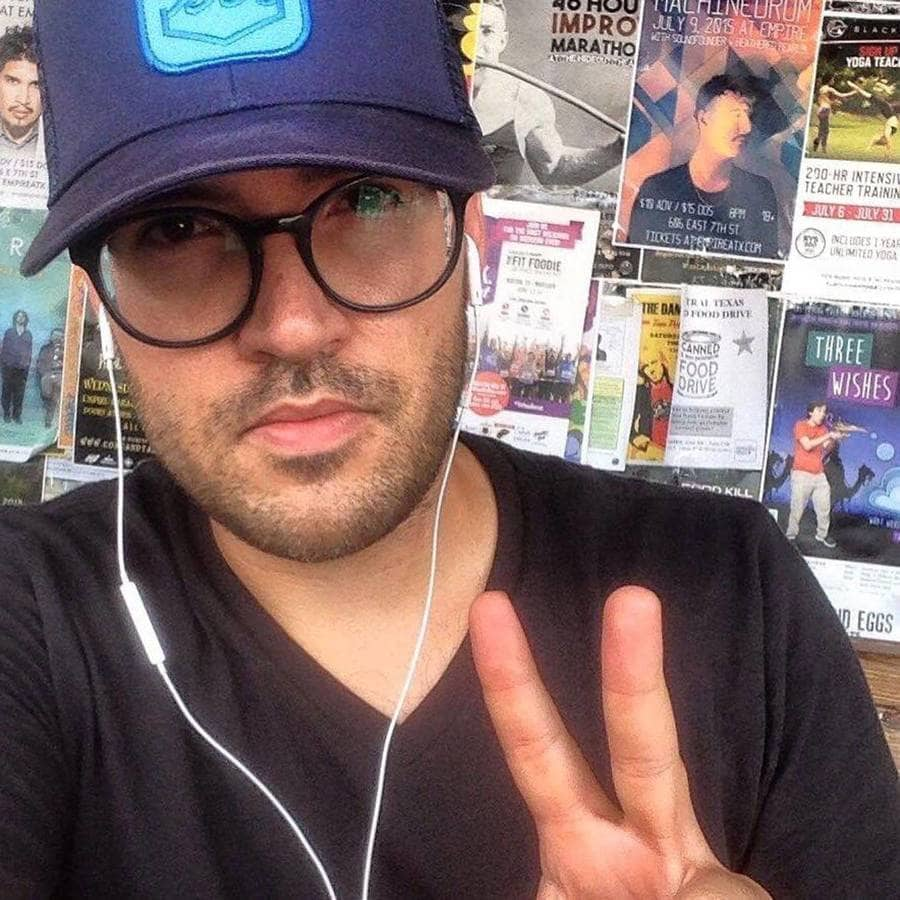 A selfie of Brandon Vezmar holding up a peace symbol with his fingers.