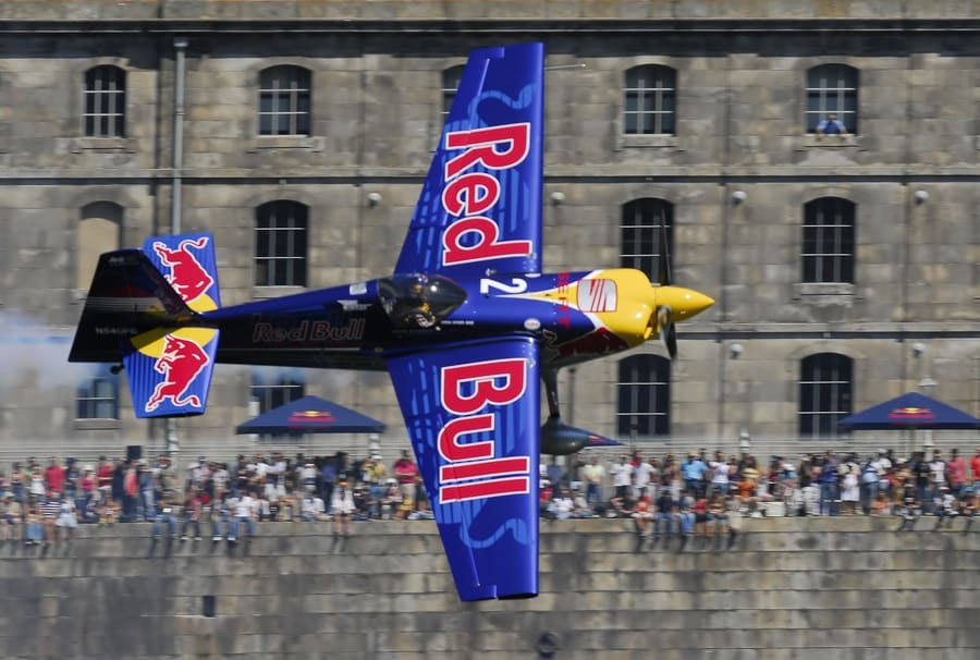 A plane with the Red Bull logo flying in the Red Bull Air Race in Portugal.