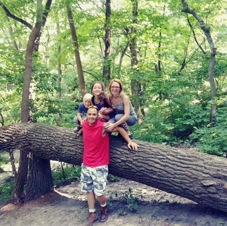 William and Christy Baxter with their children posing on a tree trunk.