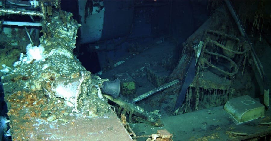 A ship's bell is visible amid the wreckage of the USS Indianapolis.