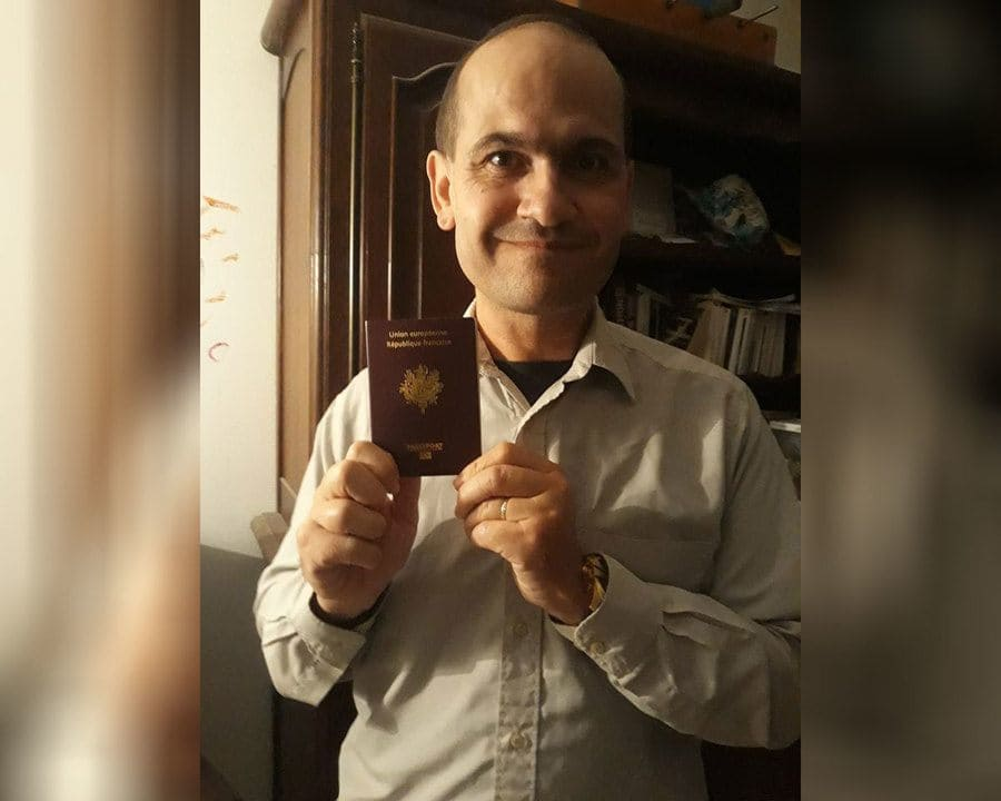 Frederic Bourdin holding up a French passport