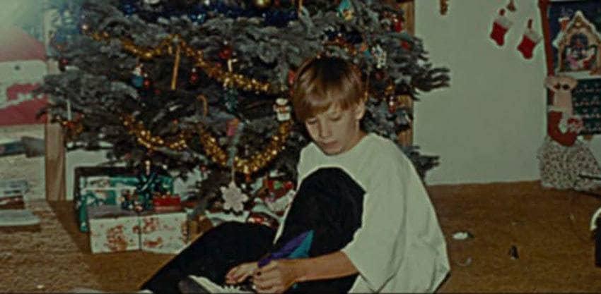 Nicholas Barclay as a boy sitting by the Christmas tree.