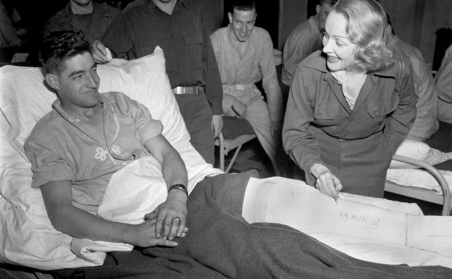Marlene Dietrich autographing the cast of a wounded soldier in Belgium, 1944.
