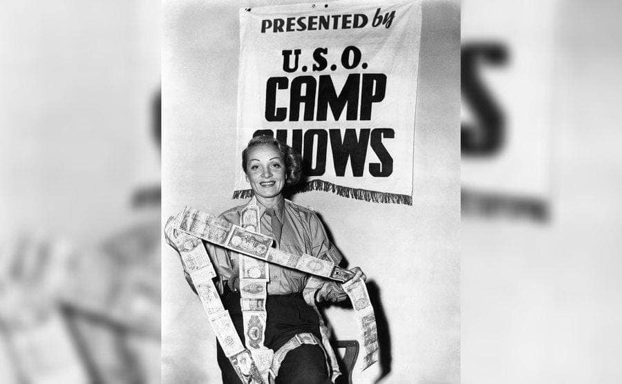 Marlene Dietrich with 'Presented by USO camp Shows' written behind her during WWII.