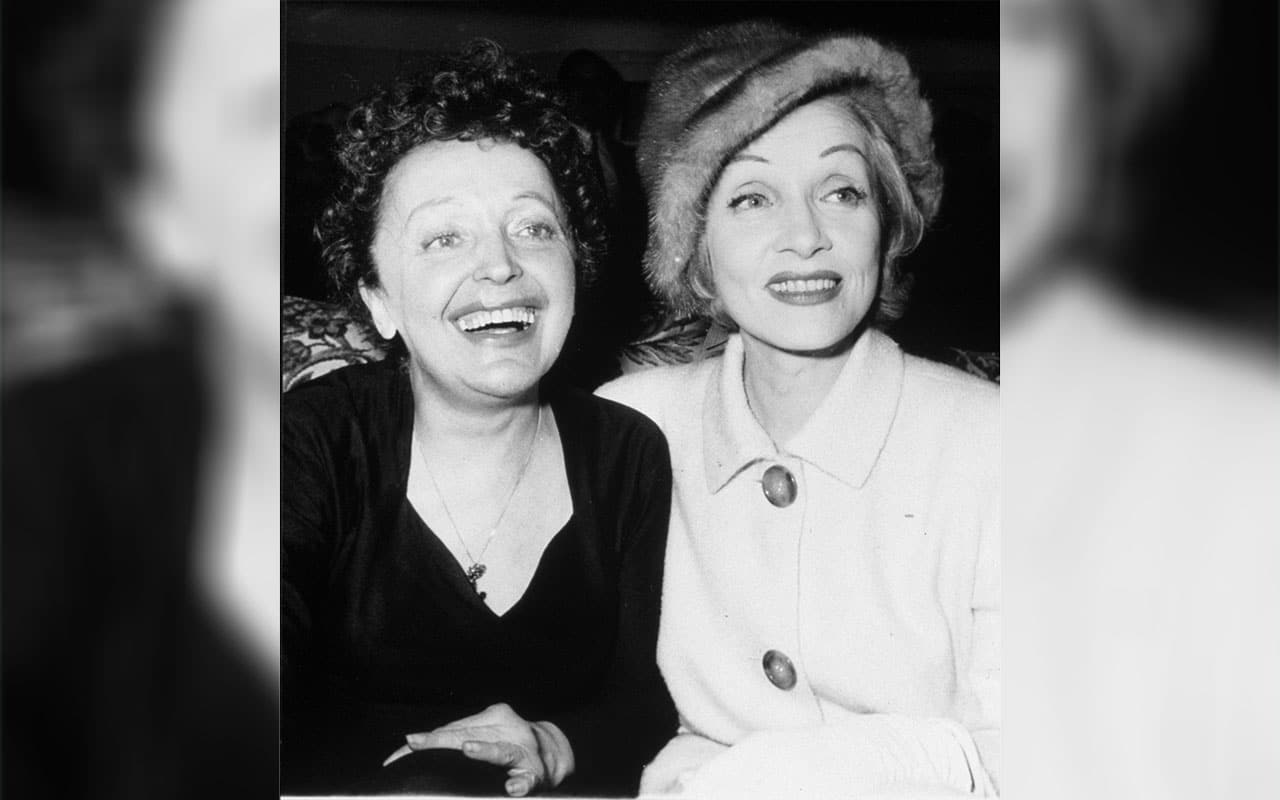 Marlene Dietrich and Edith Piaf with their arms around each other's shoulders in 1959.