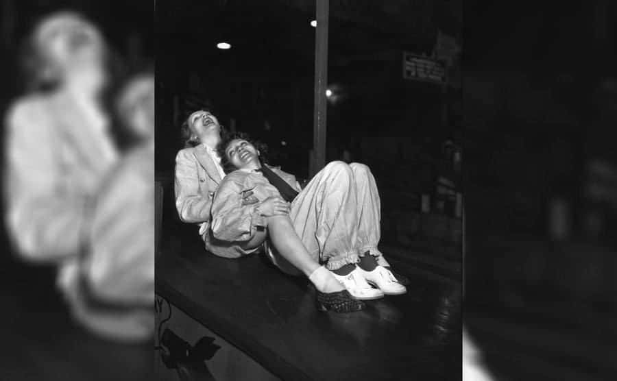 Marlene Dietrich and Claudette Colbert laying together on a table while laughing.