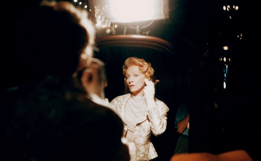 Marlene Dietrich fixing her hair in the mirror in 'The Monte Carlo Story' 1956.