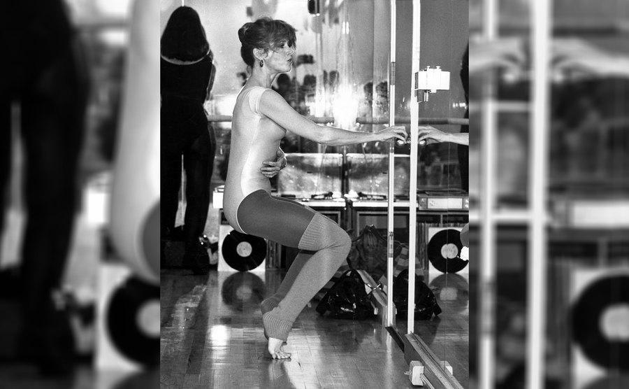 Jane Fonda warming up on her toes in front of a mirror