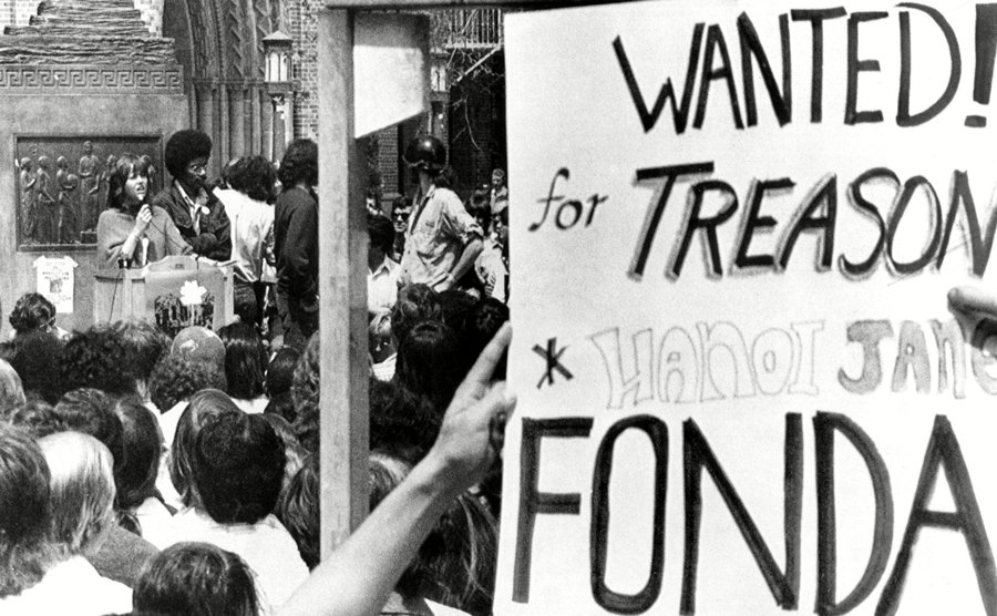 Jane Fonda was speaking while someone is holding up a sign which says 'Wanted! For Treason Hanoi Jane Fonda'