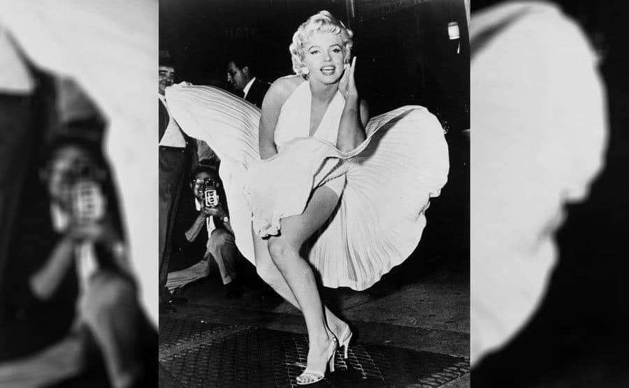 Marilyn Monroe in 'The Seven Year Itch' standing over vents in the street with her iconic white v-neck dress blowing in the air