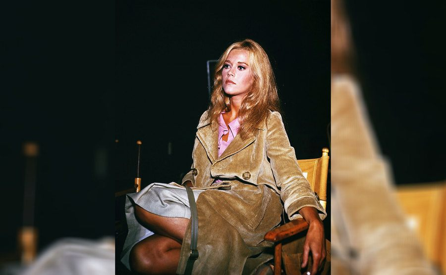 Jane Fonda wearing a long coat and a skirt past her knees sitting in a directors chair in 1966