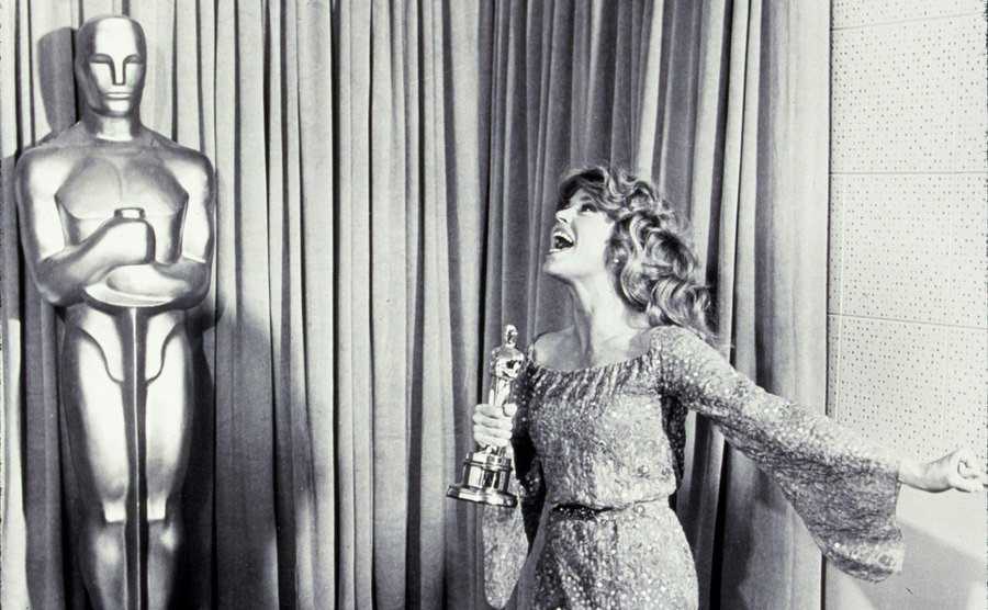 Jane Fonda at the Oscars in 1971 holding her Oscar next to a large life-sized Oscar statue