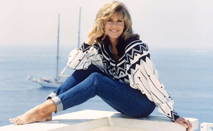 Jane Fonda sitting on a ledge overlooking the ocean with a boat in the water