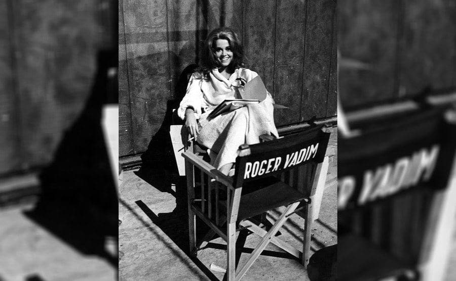 Jane Fonda behind the scenes of 'Barbarella' sitting with her feet on Roger Vadim's director's chair