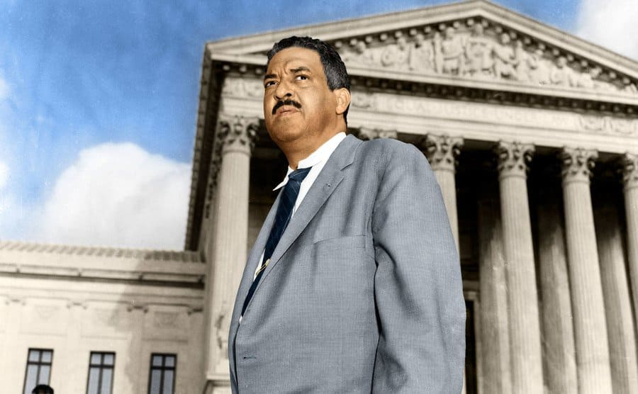 Thurgood Marshall standing in front of the Supreme Court building