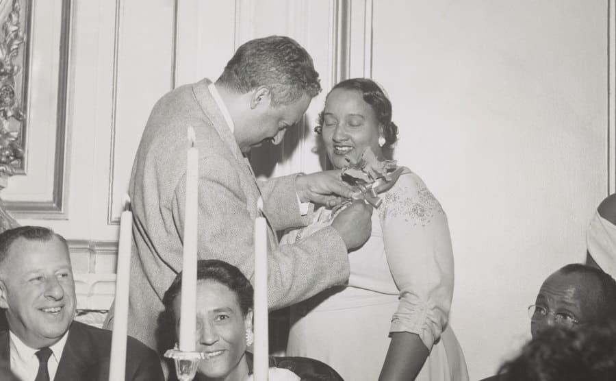 Thurgood Marshall is pinning an orchid on Mrs. Lulu White's dress at the Freedom Fund Dinner.