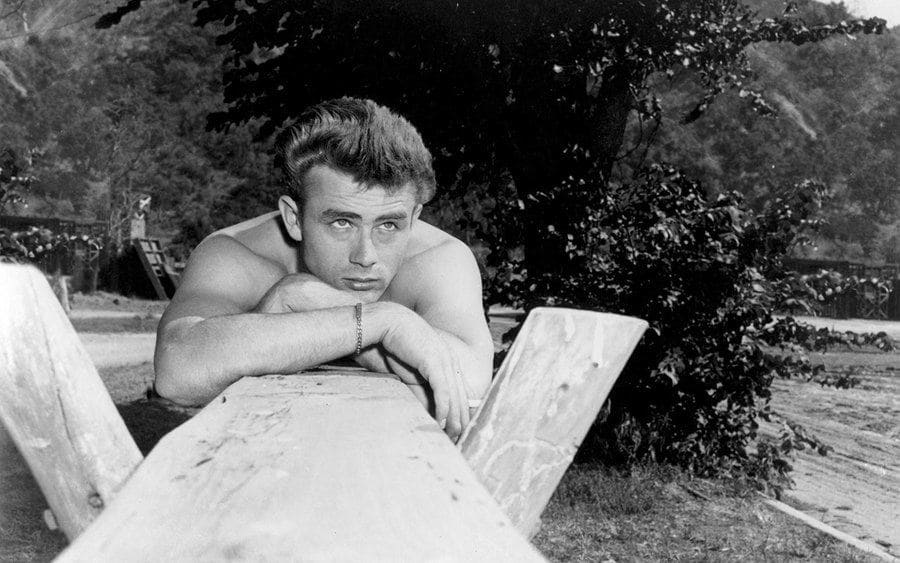 James Dean leaning on a piece of wood in 'East of Eden.'