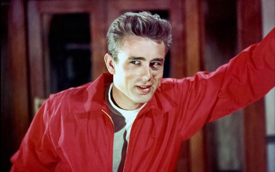 James Dean in 'Rebel Without a Cause' leaning against a wall and wearing a red jacket