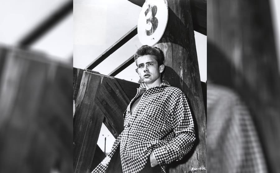 James Dean leaning against a wooden pole with a circular sign with the number three on it.