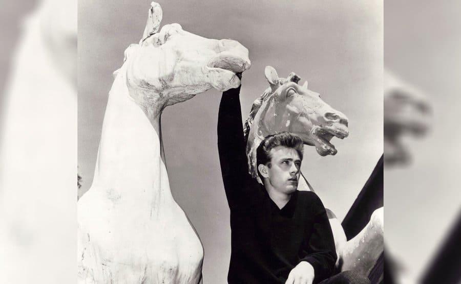 James Dean posing between statues of horses