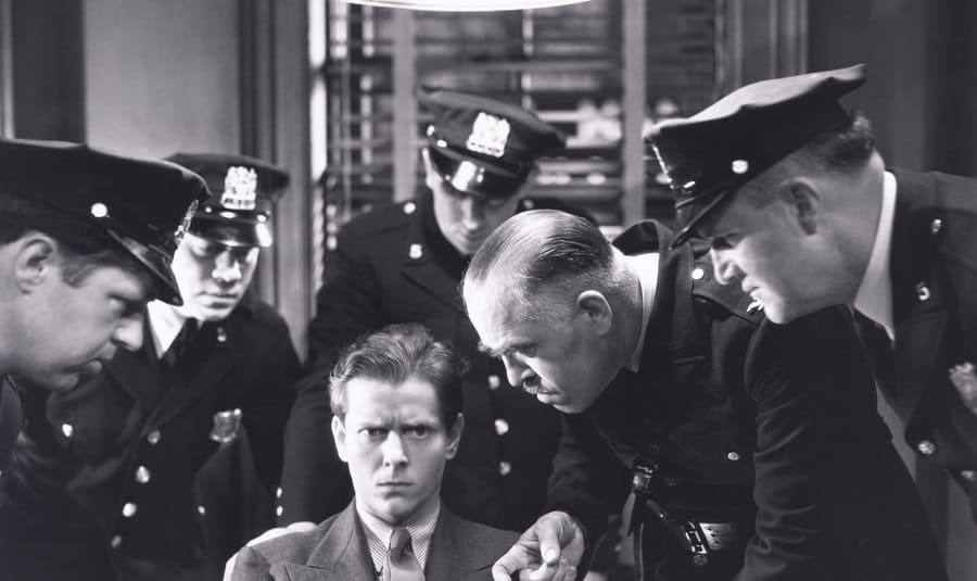 A scene from a movie with policemen interrogating a suspect