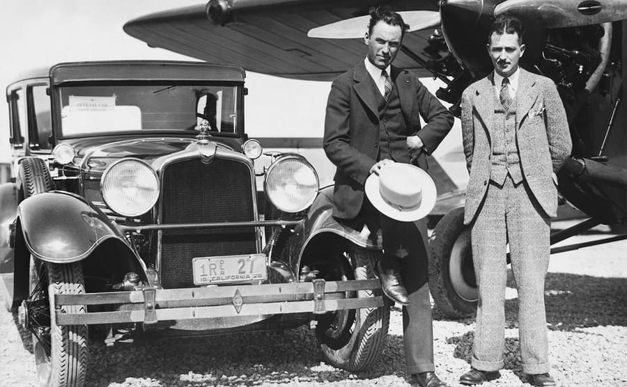 Howard Hughes and Roscoe Turner standing in front of their plane and car parked in the airport.