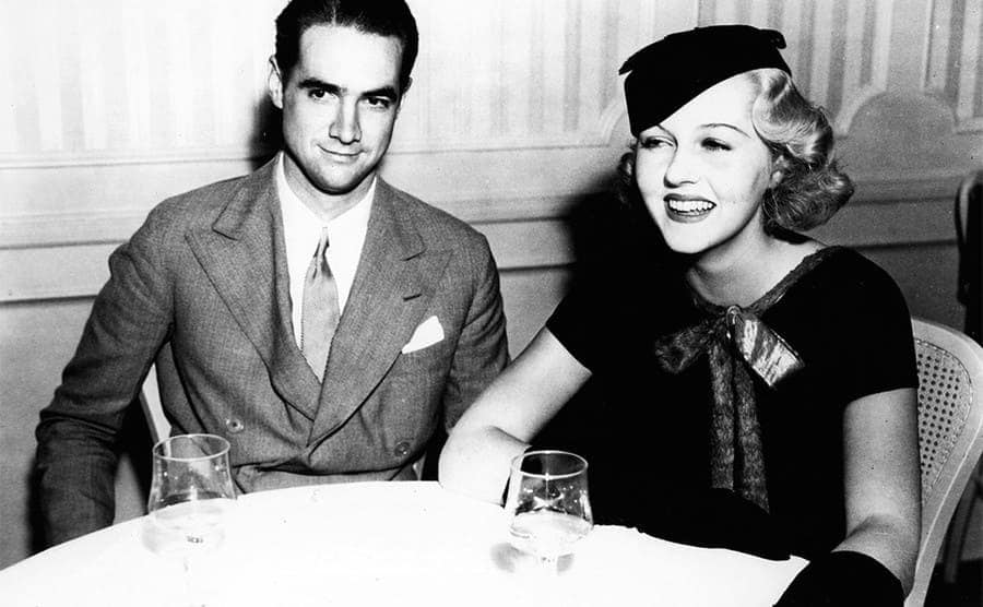 Howard Hughes and Patricia Ellis sitting at a table with wine glasses in front of them