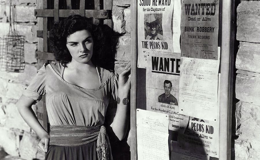 Jane Russell standing next to wanted posters put up outside of an old building in The Outlaw