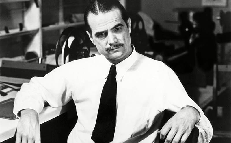 Howard Hughes sitting in a chair casually leaning on a desk