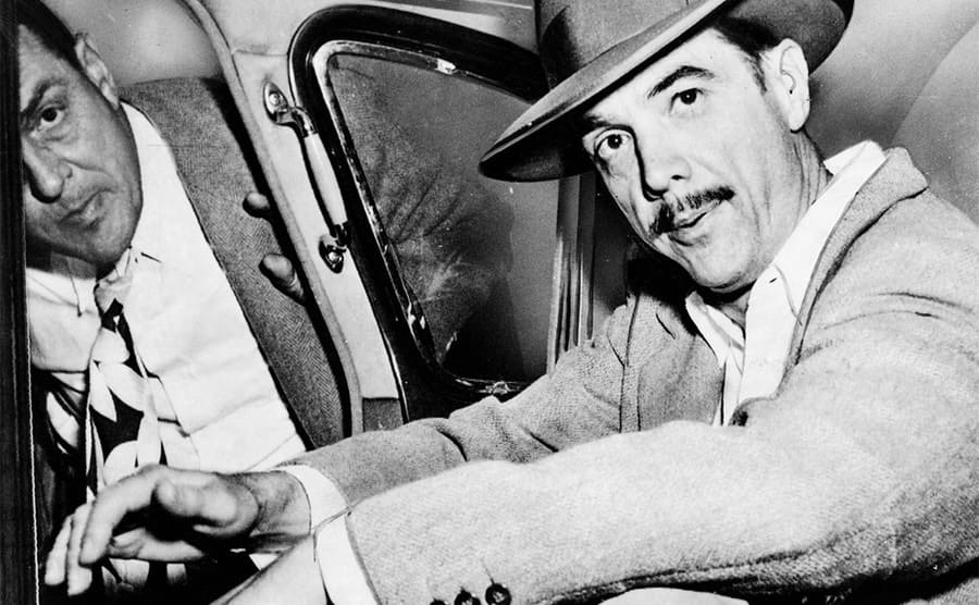 Howard Hughes sitting in the back of a car circa 1947