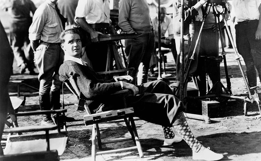 Howard Hughes on the set of the film Sky Devils with people and equipment surrounding them