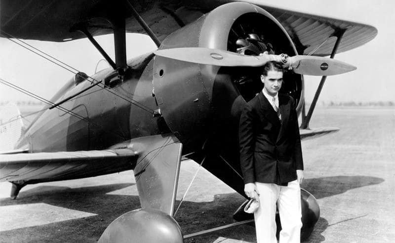 Howard Hughes posing in front of a Boeing pursuit plane