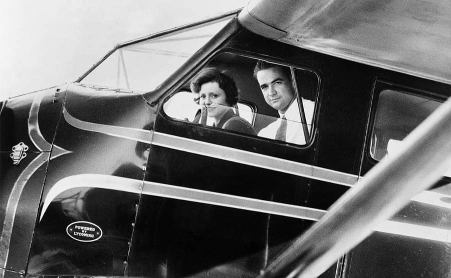 Howard Hughes next to Nancy Carroll in the cockpit of a plane