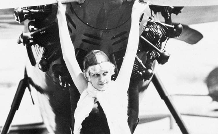 Jean Harlow standing in front of an airplane on the set of Hell's Angels