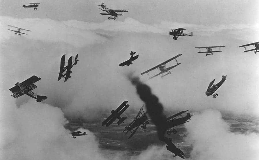 A scene from Hell's Angel's with older planes flying around the sky with one of them about to fall with black smoke coming out of it