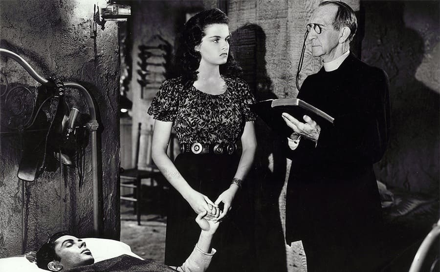 Jack Buetel lying in bed with his eyes closed, Jane Russell holding his hand, and Carl Stockdale holding a Bible in a scene from The Outlaw