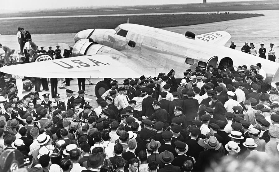 Police and people surrounding Howard Hughes plane after he landed from his 91-hour flight