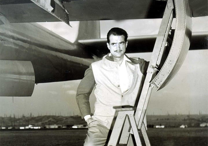 Howard Hughes standing on a ladder under an airplane with a hatch open