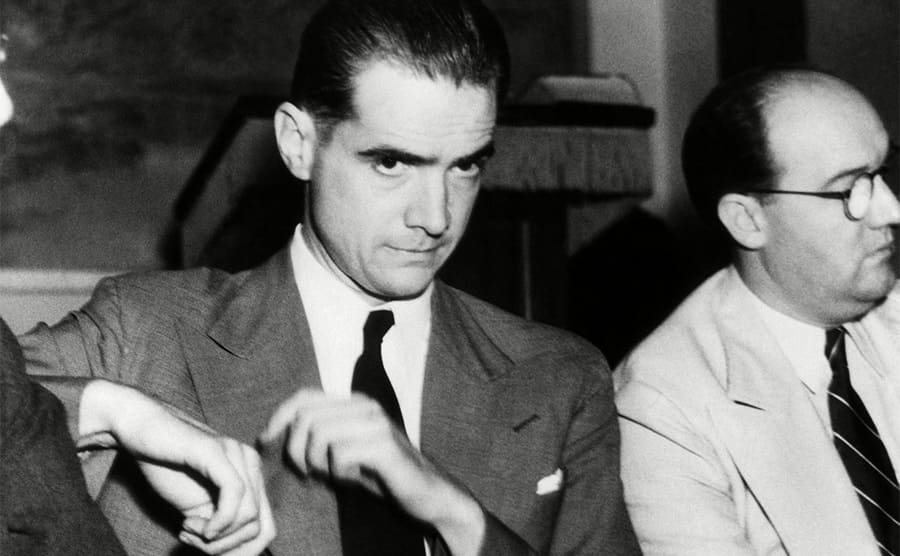 Howard Hughes sitting in court next to his lawyer