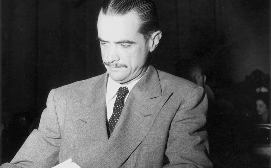 Howard Hughes sitting with a stack of papers and an intense look
