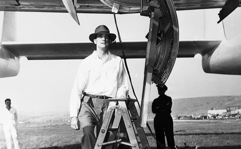 Howard Hughes working on his airplane with someone in uniform standing behind him