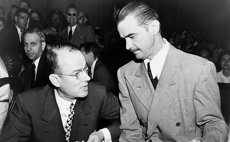 Howard Hughes conferring with his attorney in court