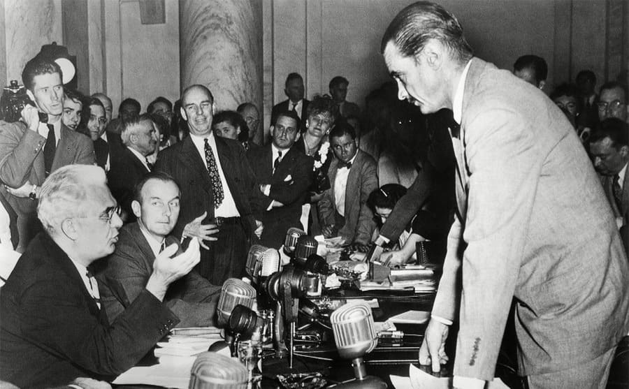 Howard Hughes conferring with Senator Homer Ferguson with people surrounding them