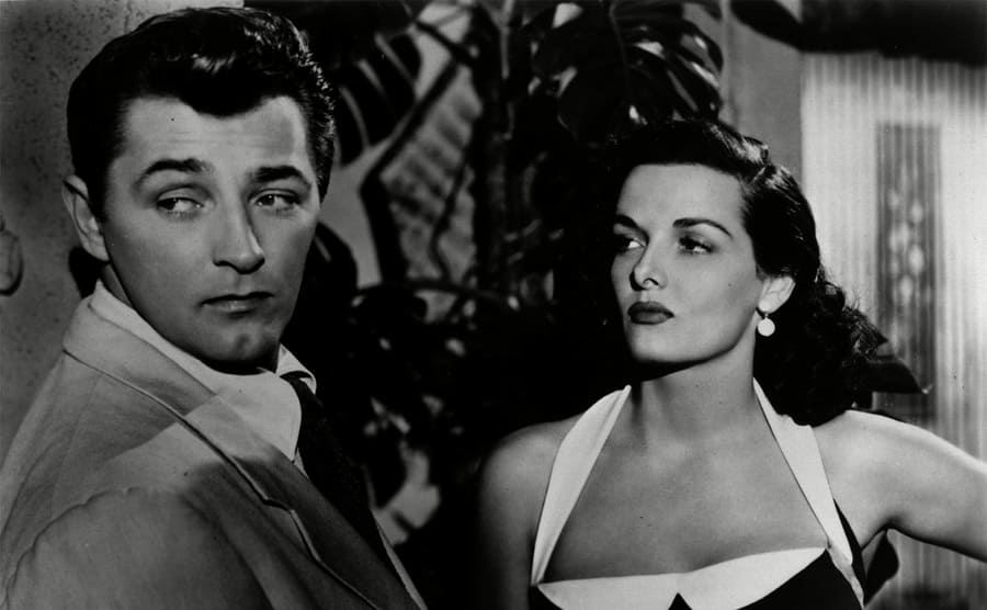 Robert Mitchum looking away from Jane Russell while she looks at him in a scene from His Kind of Woman