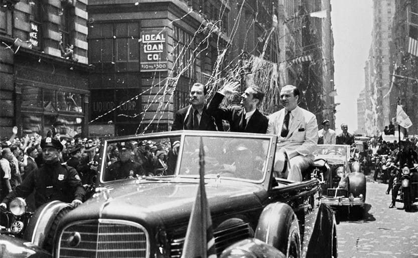 Howard Hughes in the back of a car during a parade with confetti and streamers being thrown everywhere