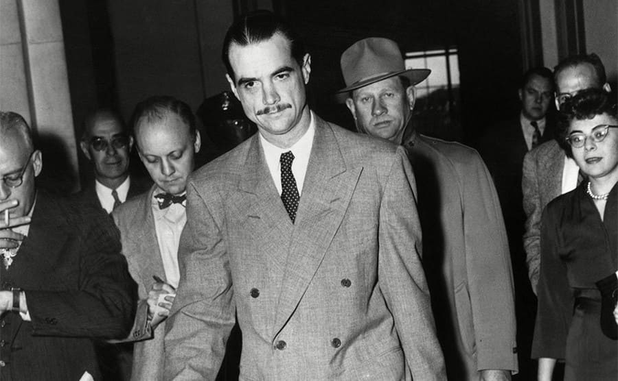 Howard Hughes wearing a suit and walking with people around him