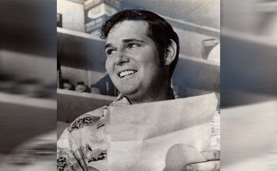 Melvin Dummar holding a piece of paper while smiling