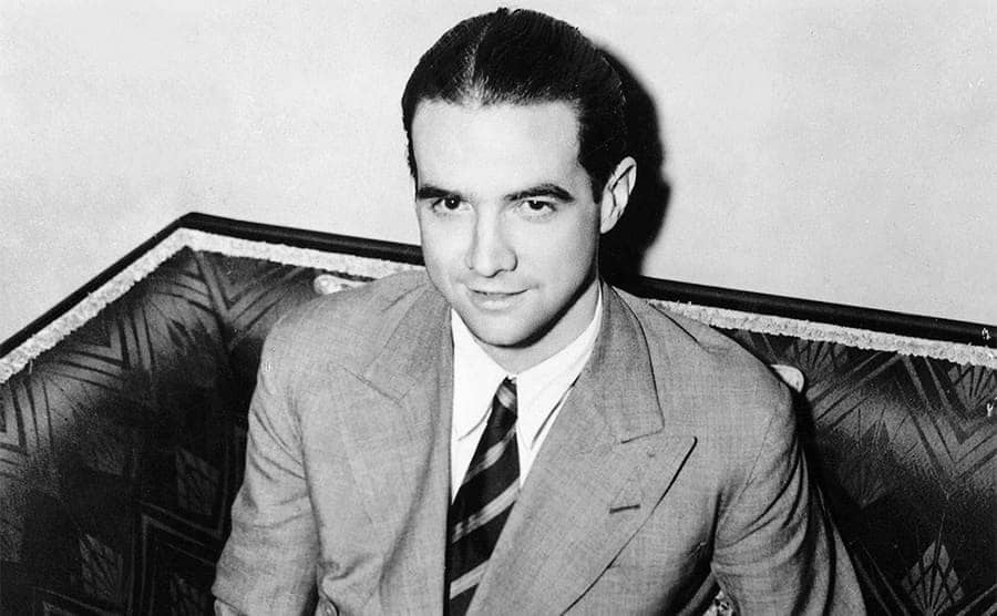 Howard Hughes sitting with a map and a pencil