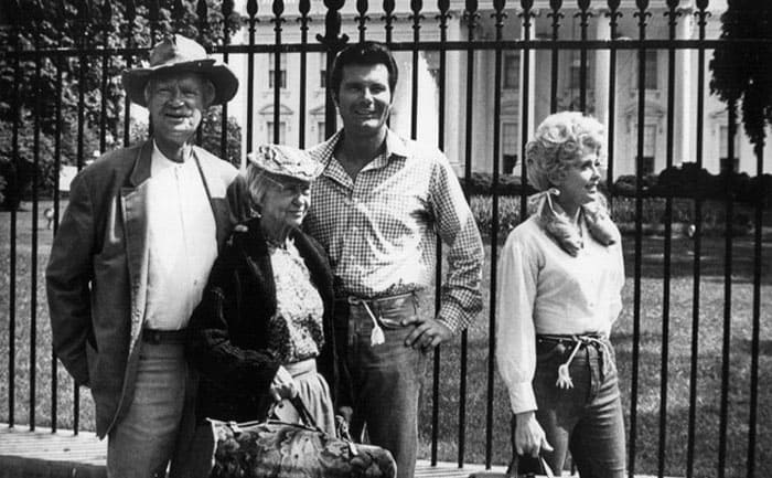 Buddy Ebsen, Irene Ryan (Granny), Max Baer Jr, and Donna Douglas standing in front of a mansion.