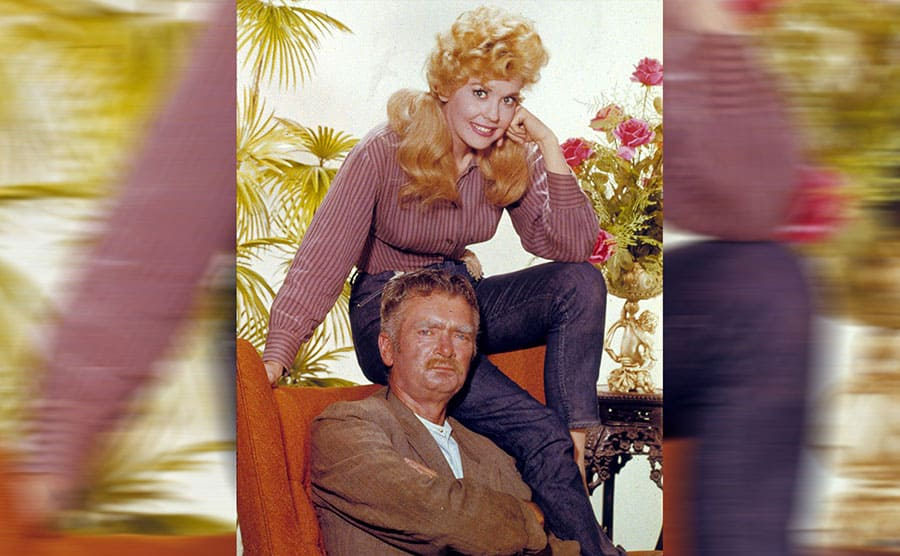 Donna Douglas sitting on the top of a chair and Buddy Ebsen sitting in the chair